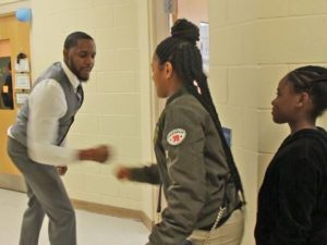Mr. White community building by performing one of his customized handshakes with a student